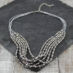 A Gorgeous Grey Thread and Bead Necklace by My Posh Shop.Features a layered mix of Gun Metal Silver and Gold beads. This unique design will finish off an outfit beautifully. A short necklace that sits high on the chest. Comes wrapped in tissue and presented in a gift box. Take a look at our full range of stylish costume jewellery.Grey Thread Chain and Beads.49 cm chain. Plus 7cm extender.
