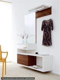 Contemporary entryway organizer with shoe storage, bench, mirror, clothes hooks and pole, shelf. In white with walnut wood accents