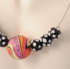 Pink yellow purple white glass  solid big bead enhanced by black and white polka dots beads. Comes in a handcrafted wooden gift box