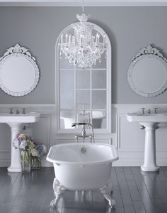 A minimalist and still beautiful bath. The stand alone tub in the middle reflects the curves in the mirrors. The mirrors are repeated in the chandelier. The edges are soft and curvy so it all ties in together. Romantic but still minimal. A great combo.