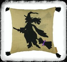 """#1963 - Flying Witch Pillow.  A wonderfully Large Burlap Pillow that is 17"""" Square with a single image of a Flying Witch adorning the front, in Halloween Black. Just a touch of bright Purple is added in Ribbon to accent the Witches' Broom. A simple Black tassel is added to each corner to give the pillow a look of sophistication. Perfect with the addition of Pillows #1964 & #1965 for a wonderful Halloween display on any couch or chair. Minimum Order: 1"""