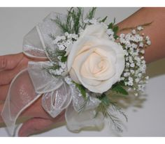 Cream rose wrist corsage. Trimmed with babies breath and sheer ribbons, a big beautiful rose bloom looks elegant on its own. Toronto florists, Helen Blakey Flowers.