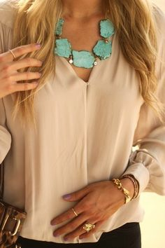 Nude blouse with a turquoise statement necklace.