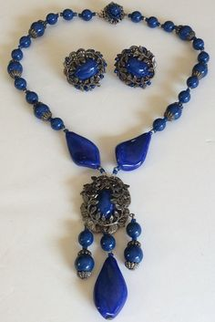 This is such a strikingly beautiful vintage jewelry set by designer Miriam Haskell. It consists of a necklace and matching earrings that are wonderfully crafted with a lovely combination of luminous pate de verre art glass stones, glistening round glass beads and lustrous faux lapis cabochon stones in a gorgeous royal blue color tone. The setting is in an exquisite antiqued silver tone filigree metal that shows beautifully in the form of twining leaves framing both the earrings faux lapiz…
