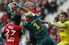 Lille's Simon Kjaer (top) fights for the ball with Nantes' goalkeeper Remy Riou and Lucas Deaux (R) during their French Ligue 1 soccer match at Pierre Mauroy Stadium in Villeneuve d'Ascq March 15, 2014. REUTERS/Pascal Rossignol
