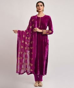A fine example of Velvet Glamour, this is a purplish magenta silk velvet suit adorned with gold tilla floral embroidery on sleeve ends and all over floral embroidered georgette dupatta. The tilla embroidery on dupatta is also embellished with seq Designer Kurtis, Designer Dresses, Red Lehenga, Anarkali, Lehenga Choli, Mode Bollywood, Bollywood Fashion, Indian Attire, Indian Ethnic Wear