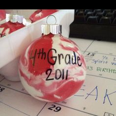 Squeeze acrylic paint into clear glass ornament, swirl around until it covers the inside, replace top, write initial, date, etc with sharpie marker and voila! Christmas gifts for my 4th graders!