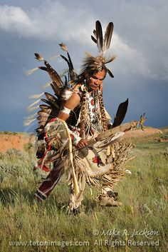 Native American People & Arts - Traditional Shoshone dancer photographed in Wyoming in full costume. Golden eagle feathers embellish the dance gear, bustle and headdress against stone cliffs and rolling hills. Native American Art, Native American Warrior, Native American Pictures, American Indian Art, American Indians, Native American Regalia, American Symbols, American Spirit, American Traditional