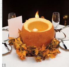 Floating candles lit hollowed-out pumpkins that were surrounded by fall leaves atop the tables, and flowers in autumnal hues adorned the fireplace mantle.