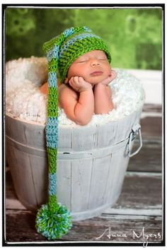 sleeping newborn propped up on hands in whitewash distress bucket with long green elf hat