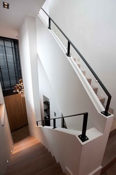 simple white & black stairway. wood stairs, black railings are same material as black frame windows & doors