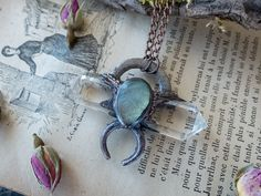 •This one of a kind statement pendant features a clear quartz crystal and a labradorite with a unique witchy design. #Labradoritejewelry #electroformedjewelry #electroformednecklace #moonchild #moonjewelry #moonnecklace #statementpendant #clearquartz #witchydesign
