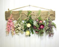 A dried flower rack is a great way to introduce some color onto your walls! This rustic dried flower rack is filled with bunches of dried flowers that have lots of color and texture, such as:  Pink larkspur Achillea Buttercream colored roses with boxwood Dark pink strawflowers with hens peppergrass Santa Cruz oregano  This drying rack measures approximately 18 long and is made from reclaimed wood. When these flowers are faded, just tie up some fresh ones and let them dry.  To see more dying…