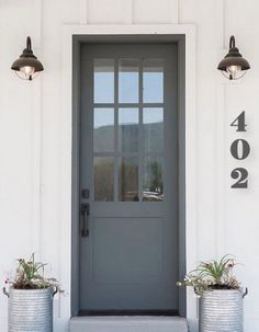 Farmhouse front door with zinc planters. Farmhouse with board and batten siding, grey front door with zinc planters. Farmhouse front door with zinc planters Millhaven Homes Painted Exterior Doors, Exterior Door Colors, Design Exterior, Painted Front Doors, Door Design, Exterior House Lights, Exterior Signage, Gray Front Door Colors, Grey Front Doors