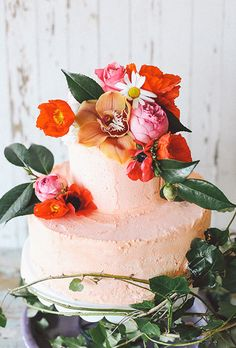 A two-tiered pink wedding cake topped with colorful peonies, poppies, ranunculus, and greenery   Brides.com