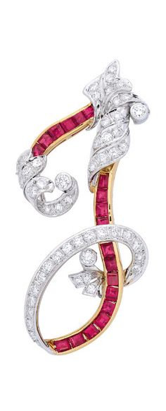 A Ruby and Diamond Pendant/ Brooch. Depicting the letter J, decorated with a ruby channel weighing approximately 1.75 carats, and round diamonds weighing approximately 2.00 carats, hidden double loop bails to the reverse, mounted in 18k white and yellow gold