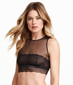 Soft-cup bra top in lace and dotted mesh for a natural shape and light support. High neckline, open back, and adjustable fasteners at back of neck and at hem.