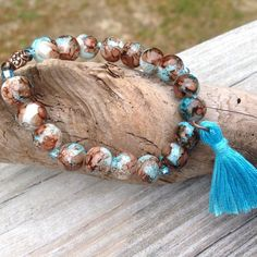 Turquoise Tassel Boho Beachy Handmade Bracelet This Turquoise Tassel Stretchy Bracelet is Handcrafted including the Tassel! Pretty molted brown, turquoise & white glass beads make this such a unique piece. Will fit wrist size 7-7.5 inches. Jewelry Bracelets