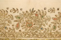 Linen rectangle with embroidered borders. Three borders,depicting flowering vines, are worked in mostly metallic thread stitch work with polychrome silk acc