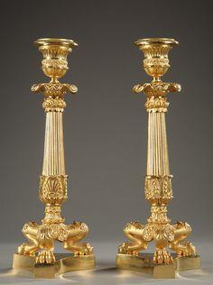 Paire de bougeoirs en bronze doré, reposant sur une base trilobée à pattes de lions. Le fût cannelé est orné en partie haute d'une bague dorée à décor de...