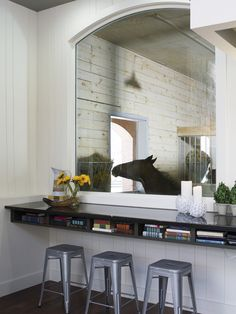 this living room in a barn house features a large window that looks into a stall. *would be great for a foaling stall!