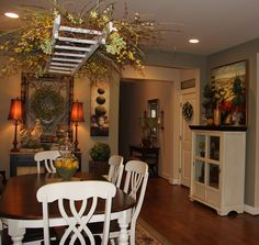 old ladder above kitchen table accessorized with lots of curly willow and floral picks