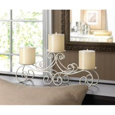 """Candleholders & Candles Home Locomotion The wrought iron framework features gorgeous flourishes that rise up to hold three pillar candles of your choice. On your mantel or tabletop, this is an effortlessly chic, elegant lighting accent. Item weight: 1.2 lbs. 16 1/8"""" x 3 1/2"""" x 6"""" high. Iron. Candles not included. UPC: 849179016982."""