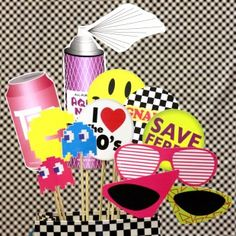 80s party photobooth props~    Tom Selleck's Mustache  Aquanet Hairspray  Smiley Face~Don't Worry Be Happy  Rubiks Cube  Pac Man & Ghosts  Phrase Buttons  Can of Tab  Sunglasses  jelly bracelets