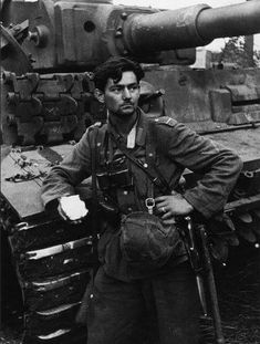 A slightly wounded soldier posing in front of a Tiger 1