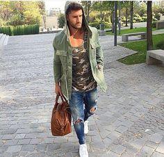 Den Look kaufen: https://lookastic.de/herrenmode/wie-kombinieren/militaerjacke-traegershirt-enge-jeans/19641   — Olivgrünes Camouflage Trägershirt  — Olivgrüne Militärjacke  — Blaue Enge Jeans mit Destroyed-Effekten  — Rotbraune Leder Sporttasche  — Weiße Niedrige Sneakers