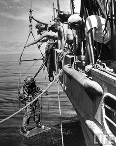 [History] A Navy diver being lowered over the side of a ship off Corregidor to recover currency dumped at sea to hide it from the invading Japanese, by Carl Mydans, 1945 ×