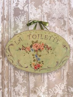 La Toilette Green with Flowers Wall Plaque Sign graces the doors of the bathrooms in my guesthouses