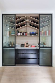 chevron pattern wine storage, behind black framed glass sliding doors.