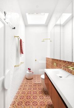 Orange and red patterned tiles contrast with white walls and a generous skylight in this narrow bathroom. Metallic hardware acts as a link between zones in this inviting bathroom space, designed and built by GIA Bathrooms & Kitchens. Orange Bathrooms, Bathroom Red, Bathroom Hacks, Bathroom Floor Tiles, Bathroom Colors, Bathroom Fixtures, Small Bathroom, Skylight In Bathroom, Master Bathroom