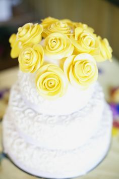 wedding cake topped with beautiful yellow roses.