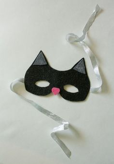 If your little one is looking for the perfect piece to finish her black cat costume, this is the mask to make. You'll need half a sheet of black glitter felt, scrap pieces of gray and pink felt, scissors, Mod Podge, a brush, a pair of glasses or sunglasses for measuring, and some sparkly ribbon.
