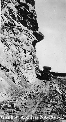1913-1914 N. T. Hagen's automobile on rock cut at Coal Camp, Sundre area, Alberta. Remarks: Beside Big Red River.