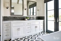 Builder Andrew Patterson ensured that the home's artful mix of finishes, including tiles from Famosa on the master bathroom's backsplash and the floor, was flawlessly executed. Ralph Lauren Home hurricane sconces flank a pair of custom mirrors. The Rohl faucets are from Pirch.