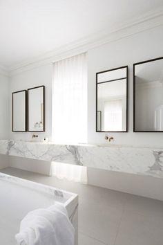 jolie salle de bain en marbre blanc, miroirs muraux,