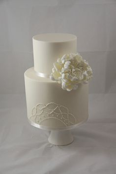 All white wedding cake with peony and piping