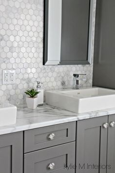 Formica 180FX Calacatta marble laminate countertop, hexagon mosaic marble backsplash and Chelse Gray vanity in ensuite bathroom with raised sinks by Kylie M Interiors Tap the link now to see where the world's leading interior designers purchase their beautifully crafted, hand picked kitchen, bath and bar and prep faucets to outfit their unique designs.