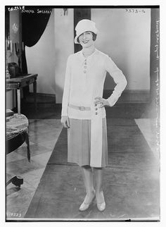 In 1927, Norma Shearer is wearing a short, button down dress, with a slightly tilted hat, a pearl necklace, and high heels.
