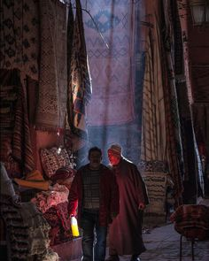 Morocco. #Marrakesh. Falling light over the carpet soukh with a man holding a yellow bottle. © #Abbas/#MagnumPhotos.