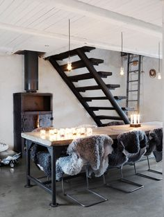Basement. yes please...the open stairs, the sheep skin chair covers, the boxy wood stove and the industrial wood table. Winter would be okay in this space.