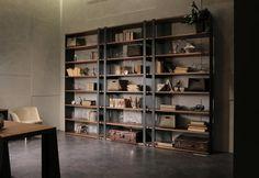 Libreria OperaPrima di MaxDivani su progetto dell'architetto Giovanna Azzarello. Contrasto di materiali e sensazioni: il freddo del ferro e il calore del legno noce trattato naturale. Multifunzionale, componibile - estensibile all'infinito