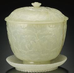 TWO MUGHAL-STYLE JADE WARES  QING DYNASTY, 19TH CENTURY  both thinly carved, the first a dish with the interior carved as an open chrysanthemum flower with two rows of fluted petals radiating from the central disk to the scalloped rim, the second a U-shaped jar and cover, the exteriors carved with arabesque floral scrolls, all surmounted by a chrysanthemum-form finial (3)  Diameter 3 5/8  in., 9.2 cm