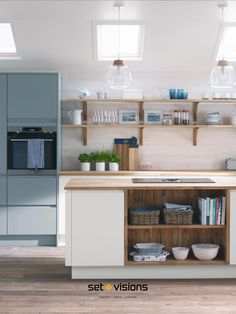 Laidback kitchen style mixing white washed cladding, off white units and soft blue cabinetry. Oak shelving complements the solid oak worktops. Accessories with simple glass pendant lights and wicker storage baskets.