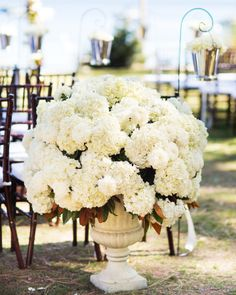 Hydrangeas and Magnolia in Concrete Urn | photography by http://www.jyweddings.com