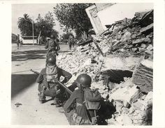 1943- U.S. patrol awaits the order to move forward while another patrol moves ahead to reconnoiter during street fighting in Bizerte, Tunisia.