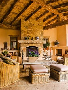 Tuscan Dream   A natural-stone surround allows this rustic-look fireplace to blend with this home's Tuscan aesthetic. The reddish-orange hues of the fireplace surround echo the color of the home's stone veneer, the patio flooring, and the weathered finish of the wooden ceiling beams.